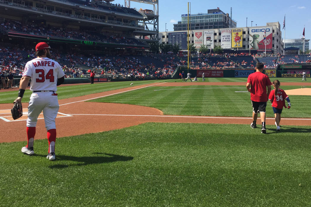 Las Vegas' Bryce Harper and fellow Las Vegan Hailey Dawson (and her brother, Zach) head onto the field where she threw out the ceremonial first pitch before the June 11 game between the Washington ...