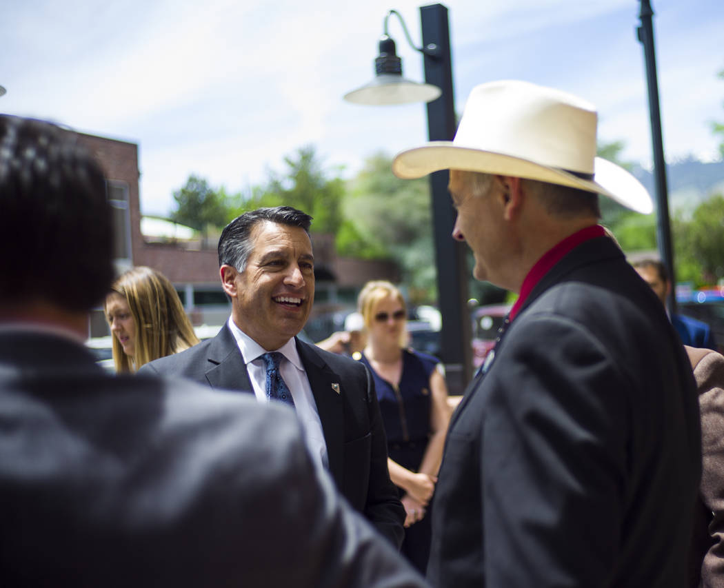 Gov. Brian Sandoval, left, talks with Sen. James Settelmeyer, R-Minden, before signing Assembly Bill 431 at The Union restaurant and brewery in Carson City on Monday, June 5, 2017. The bill nearly ...