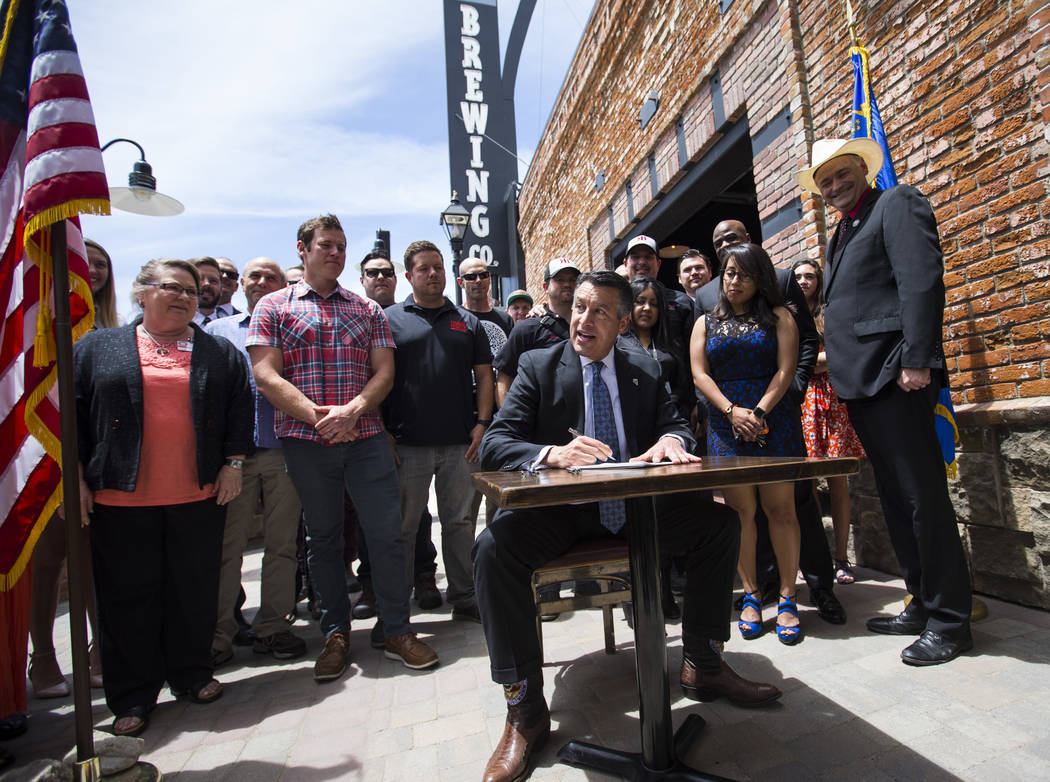 Gov. Brian Sandoval signs Assembly Bill 431 at The Union restaurant and brewery in Carson City on Monday, June 5, 2017. The bill nearly triples the number of barrels a craft brewery or brewpub can ...