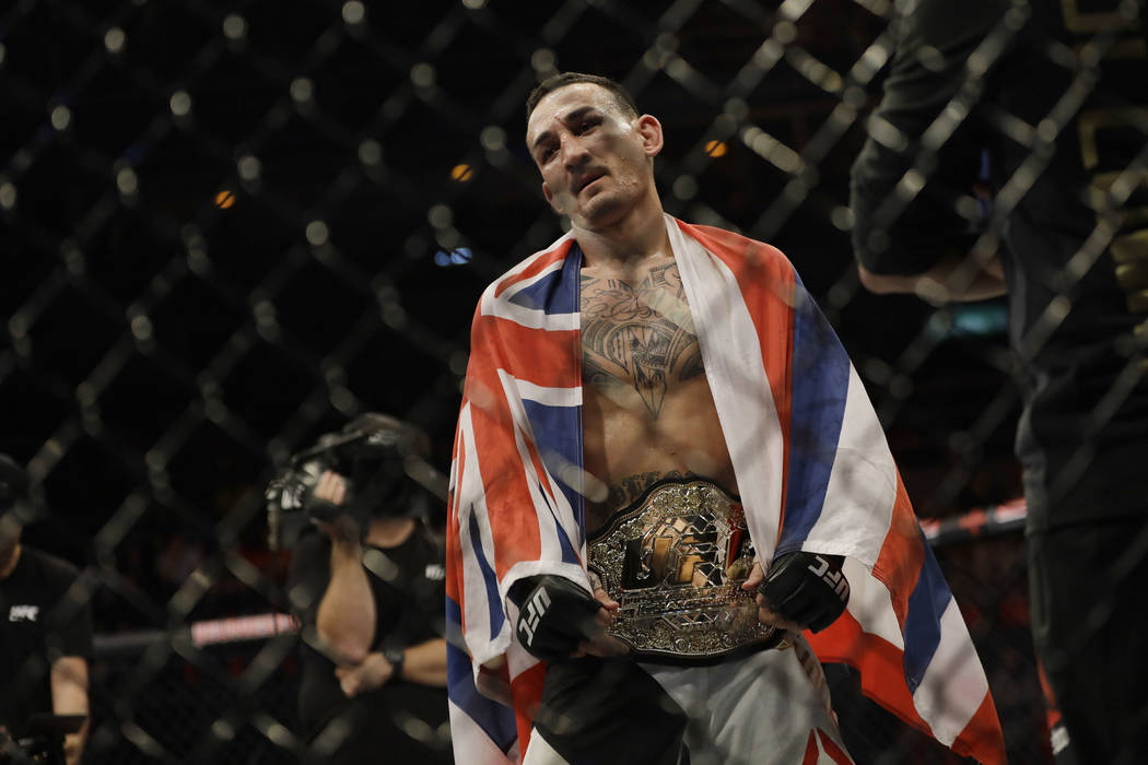 Max Holloway, of the United States, wears a champion's belt after defeating Jose Aldo, of Brazil, during their UFC featherweight mixed martial arts bout in Rio de Janeiro, Brazil, early Sunday, Ju ...