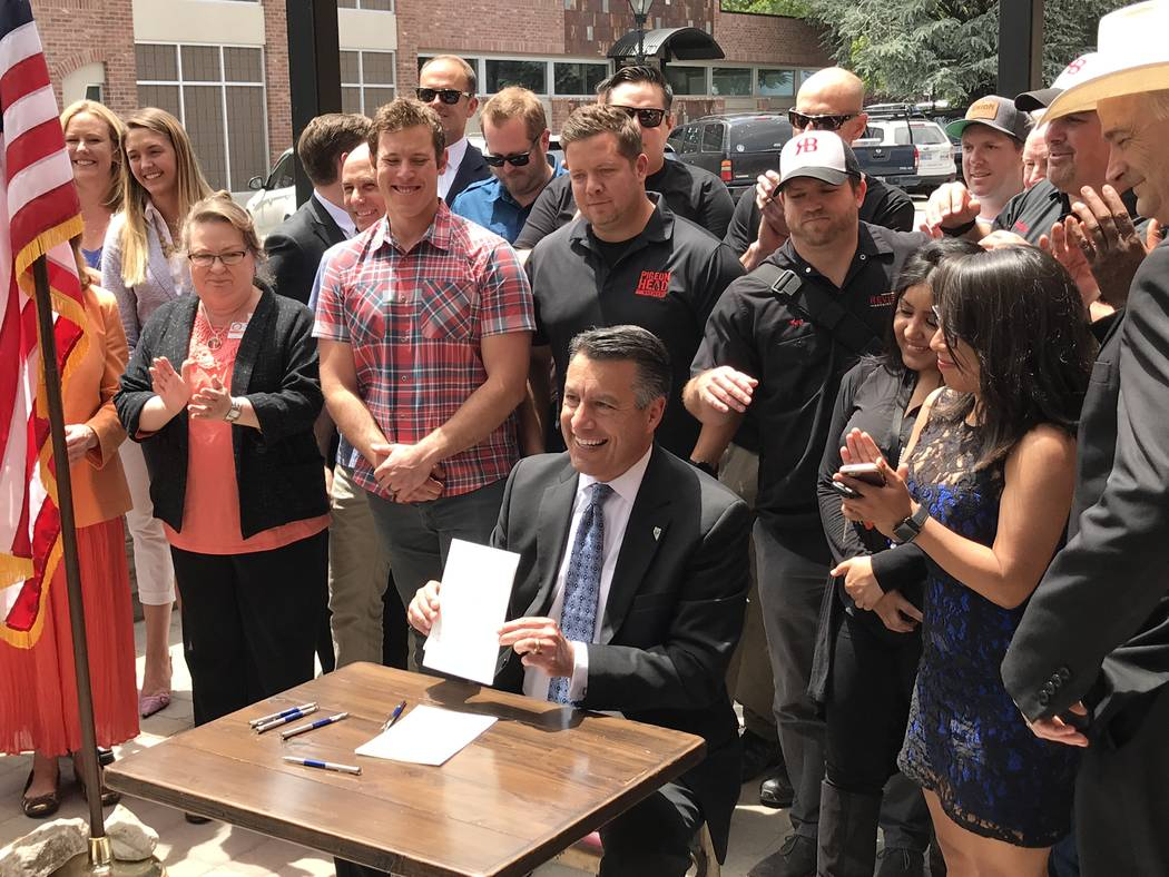 Gov. Brian Sandoval signs Assembly Bill 431, which allows brew pubs to sell more beer, at The Brewery in Carson City on June 5, 2017. (Photo by Steve Sebelius)