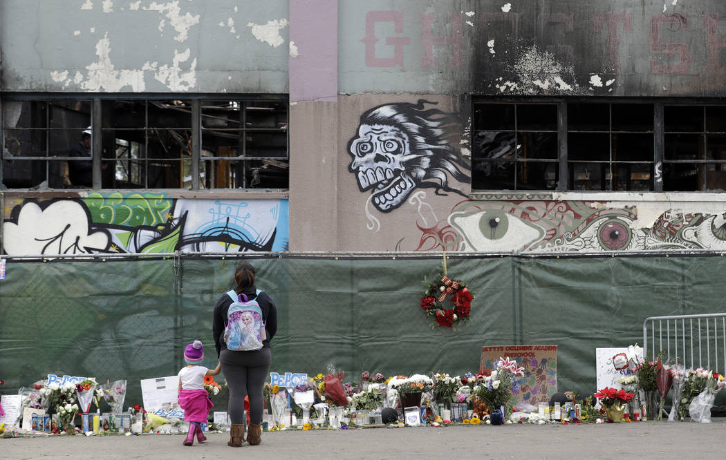 File - In this Dec. 13, 2016, file photo, flowers, pictures, signs and candles, are placed at the scene of a warehouse fire in Oakland, Calif. A source close to the investigation tells The Associa ...
