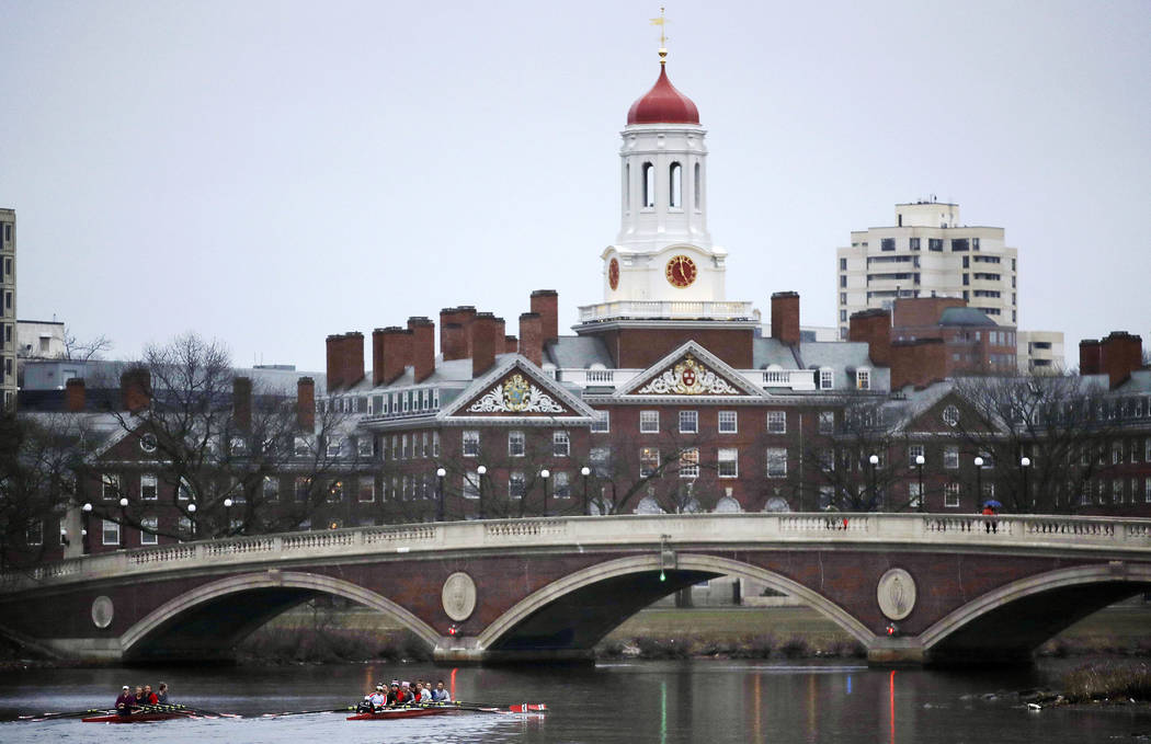 Rowers paddle along the Charles River past the Harvard College campus in Cambridge, Mass., in March 7, 2017. The Harvard Crimson, the school's student newspaper, reported June 4, 2017, that Harvar ...