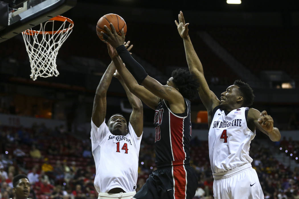 UNLV guard Jovan Mooring (30) goes to the basket between San Diego State forward Zylan Cheatham (14) and guard Dakarai Allen (4) during a Mountain West Conference tournament basketball game at the ...