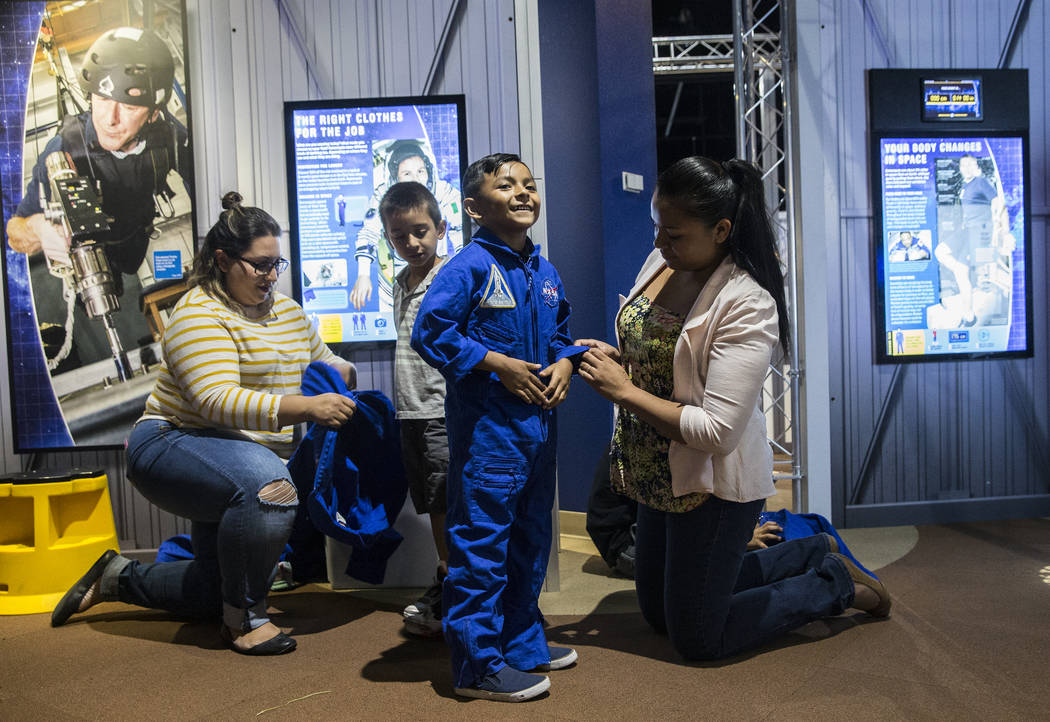 "Ela Garcia, right, helps Eli Camacho get into his replica NASA flight suit during a special members viewing day at the new ""Astronaut"" exhibit on Sunday, June 11, 2017, at Spring ..."