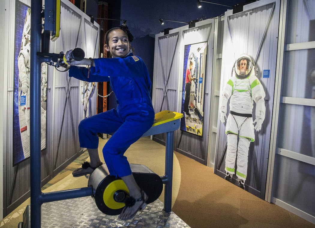 "Auminay Wise peddles a stationary bike designed to help combat muscle fatigue in space during a special members viewing day at the new ""Astronaut"" exhibit on Sunday, June 11, 201 ..."
