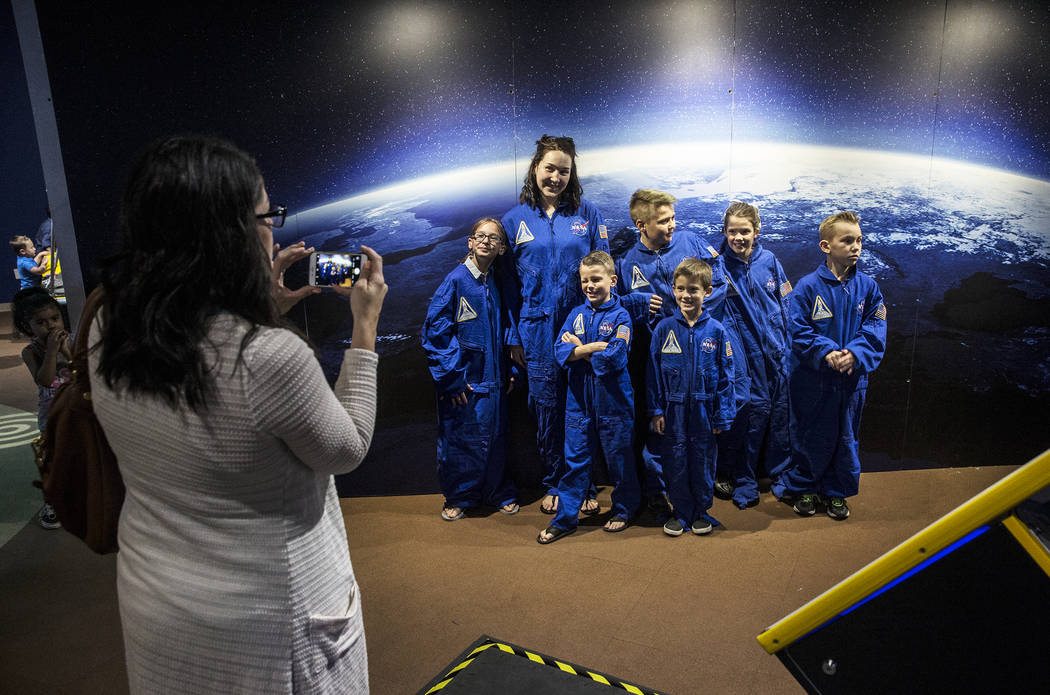 "Tiffany Cox, left, takes a photo of her family during a special members viewing day at the new ""Astronaut"" exhibit on Sunday, June 11, 2017, at Springs Preserve, in Las Vegas. Be ..."