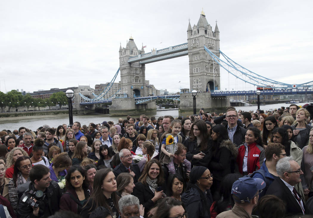 People attend a vigil for victims of Saturday's attack in London Bridge, at Potter's Field Park in London, Monday, June 5, 2017. Police arrested several people and are widening their investigation ...