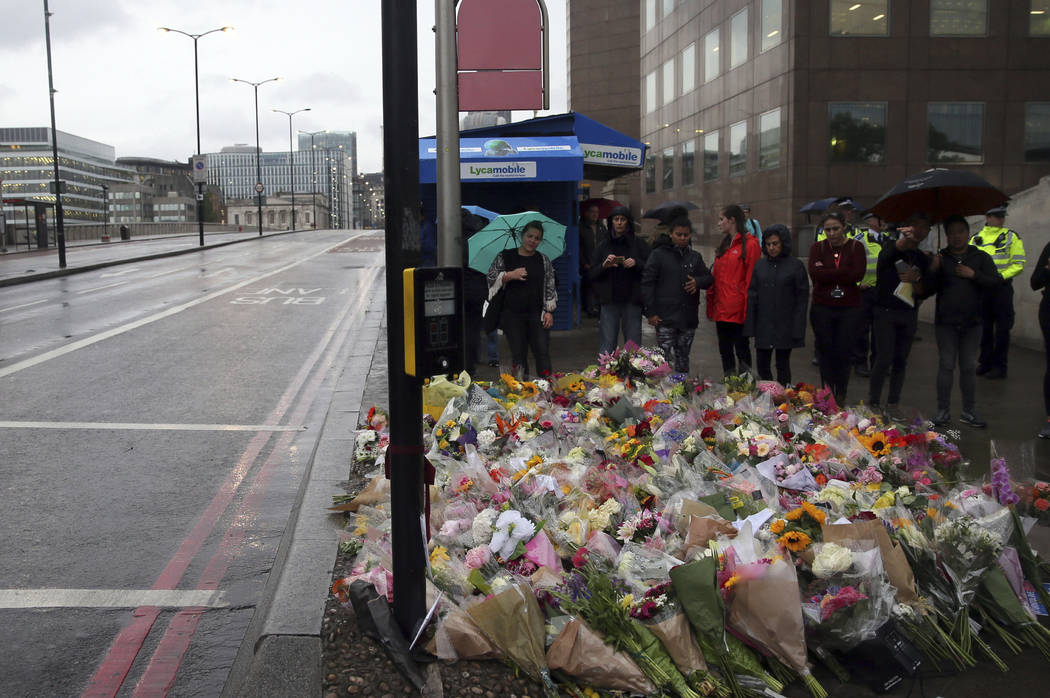 People lay flowers for victims of Saturday's attack on London Bridge, Monday, June 5, 2017. Police arrested several people and are widening their investigation after a series of attacks described  ...