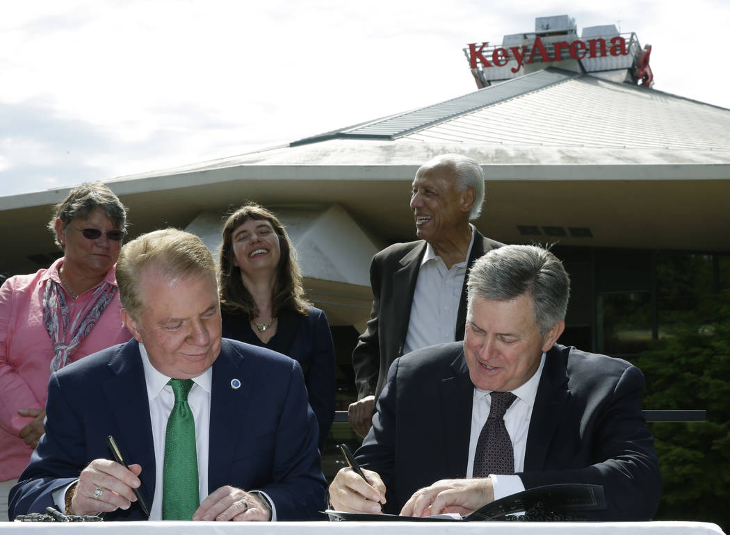 Seattle Mayor Ed Murray, left, and Tim Leiweke, right, CEO of the Oak View Group take part in a signing ceremony during during a news conference, Wednesday, June 7, 2017, in Seattle. Murray said t ...
