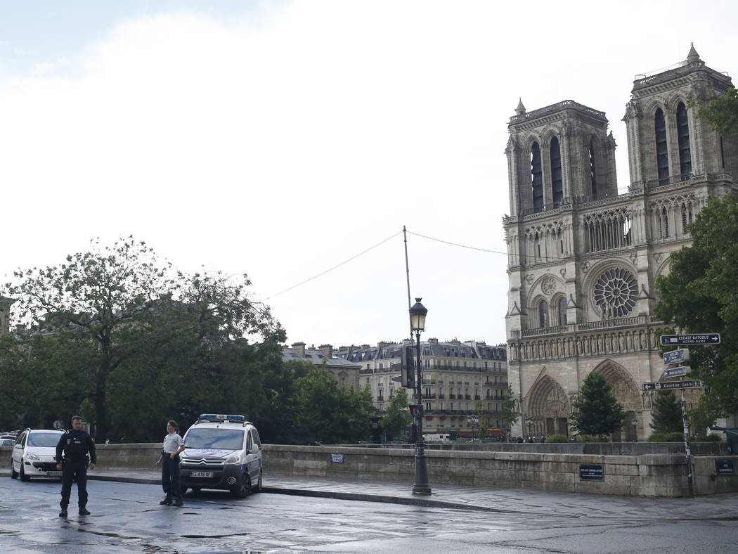 Police officers seal off the access to Notre Dame cathedral in Paris, Tuesday, June 6, 2017. Paris police say an unidentified assailant has attacked a police officer near the Notre Dame Cathedral, ...