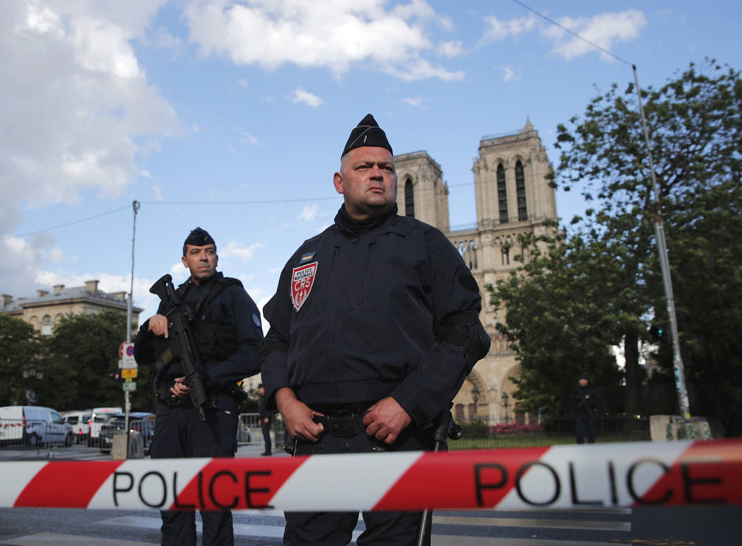 Police officers seal off the access to Notre Dame cathedral, seen in the background, after a man attacked officers with a hammer outside the famous landmark, in Paris, France, Tuesday, June 6, 201 ...