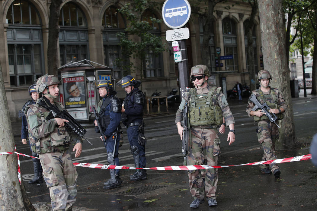 Police officers and soldiers seal off the access to Notre Dame cathedral after a man attacked officers with a hammer while patrolling the esplanade in front of the famous landmark, in Paris, Franc ...