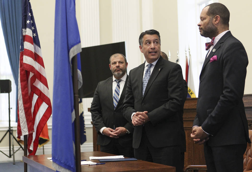 Gov. Brian Sandoval, center, speaks before signing a group of bills while flanked by Assembly Minority Floor Leader Paul Anderson, R-Las Vegas, left, and Senate Majority Leader Aaron Ford, D-Las V ...