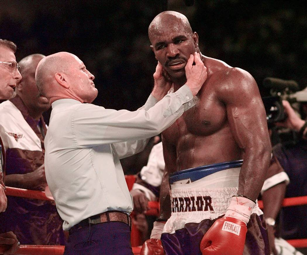 Evander Holyfield has his right ear checked by referee Mills Lane after he was bit in the ear by Mike Tyson in the third round of their WBA Heavyweight match Saturday, June 28, 1997, at the MGM Gr ...
