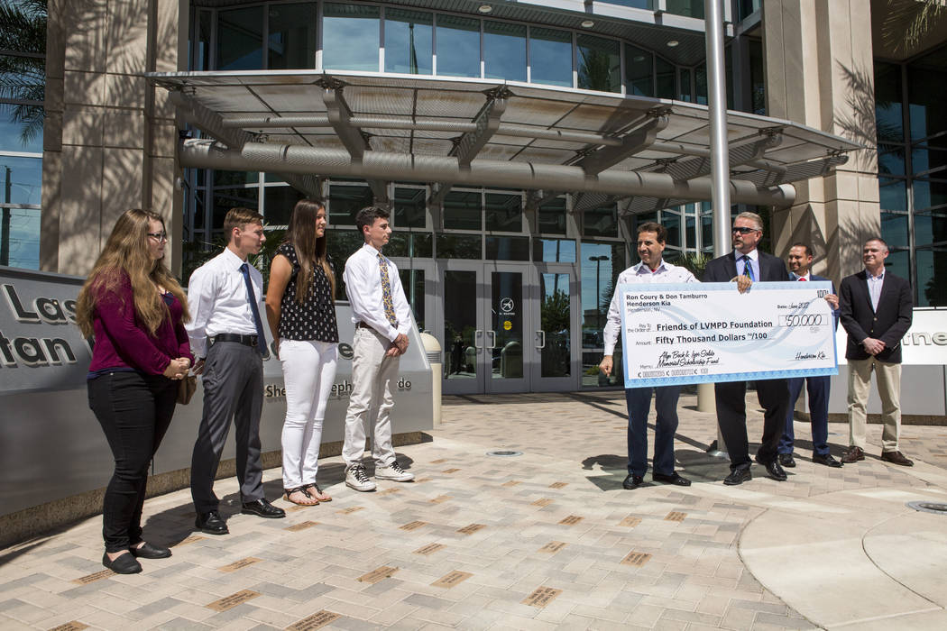 Ron Coury, co-owner of Henderson Kia and Friends of LVMPD Foundation Board member, presents a check for $50,000 to award ten high school graduates and college students scholarships of $5,000 each  ...