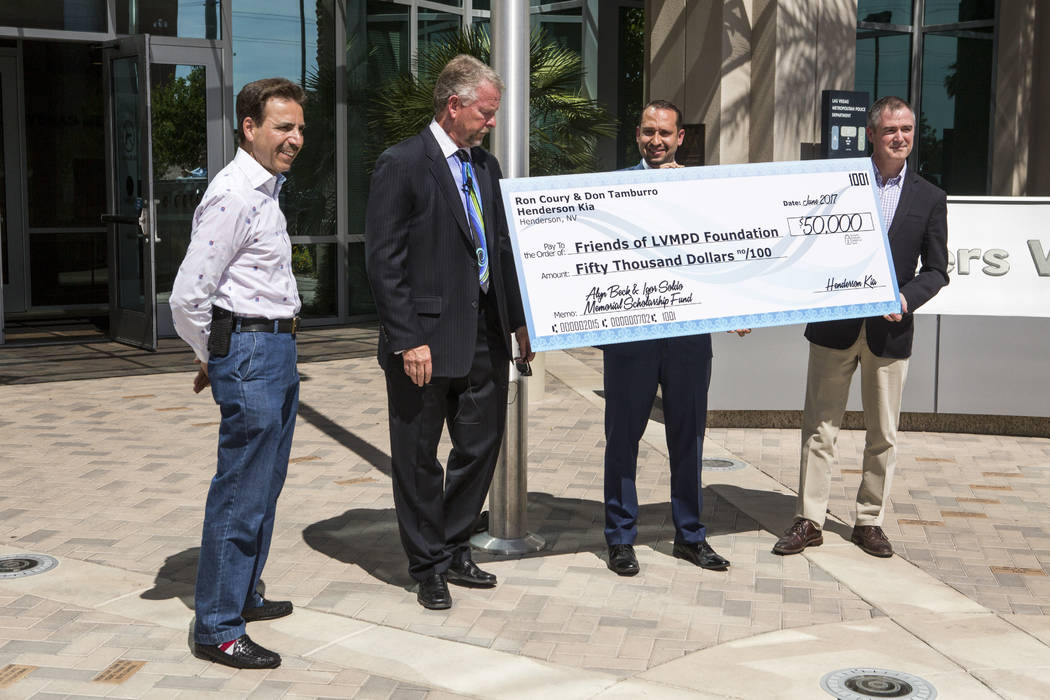 Ron Coury, left, co-owner of Henderson Kia and Friends of LVMPD Foundation Board member, presents a check for $50,000 to award ten high school graduates and college students scholarships of $5,000 ...