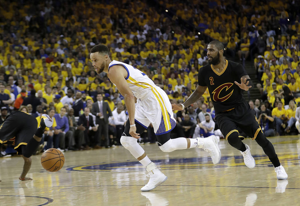 Golden State Warriors guard Stephen Curry, left, dribbles past Cleveland Cavaliers guard Kyrie Irving (2) during the first half of Game 2 of basketball's NBA Finals in Oakland, Calif., Sunday, Jun ...