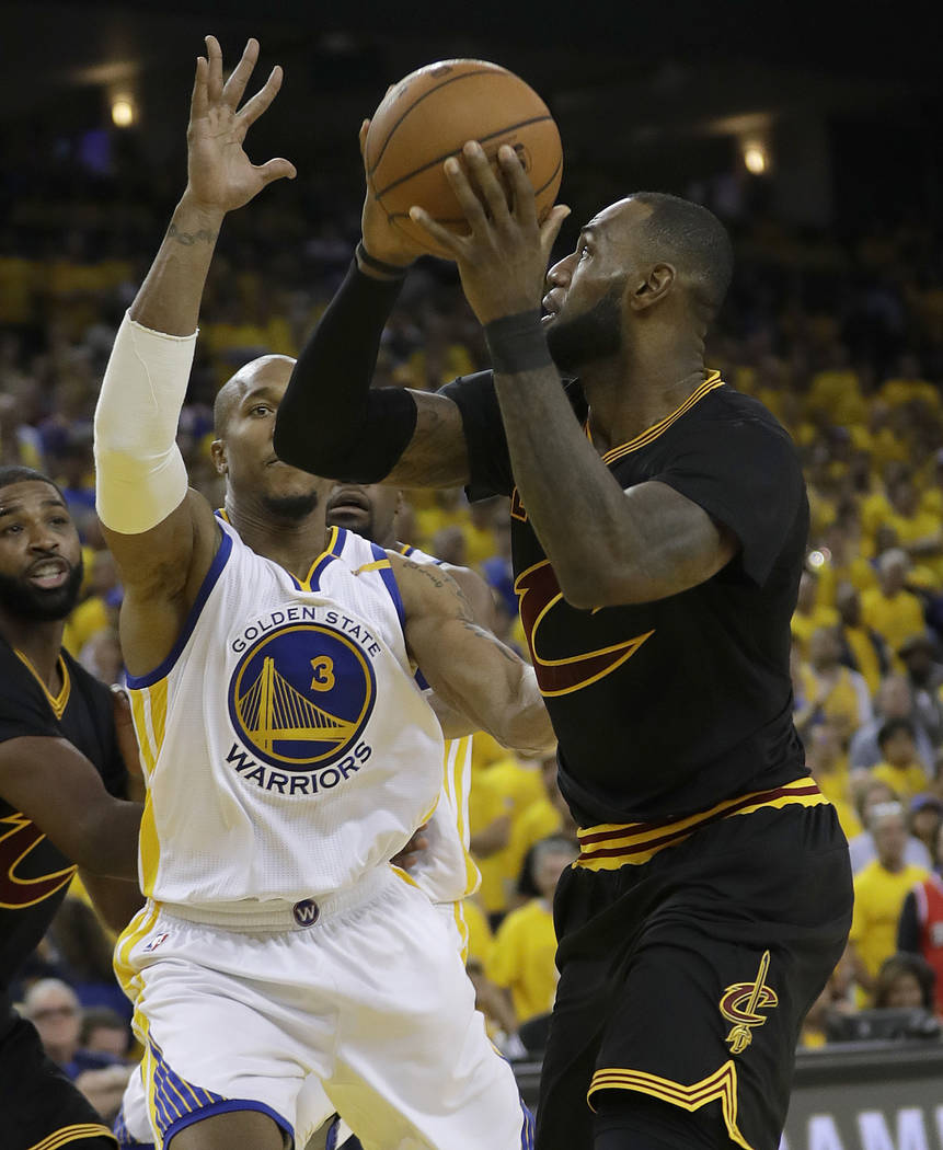 Cleveland Cavaliers forward LeBron James, right, shoots against Golden State Warriors forward David West (3) during the second half of Game 2 of basketball's NBA Finals in Oakland, Calif., Sunday, ...