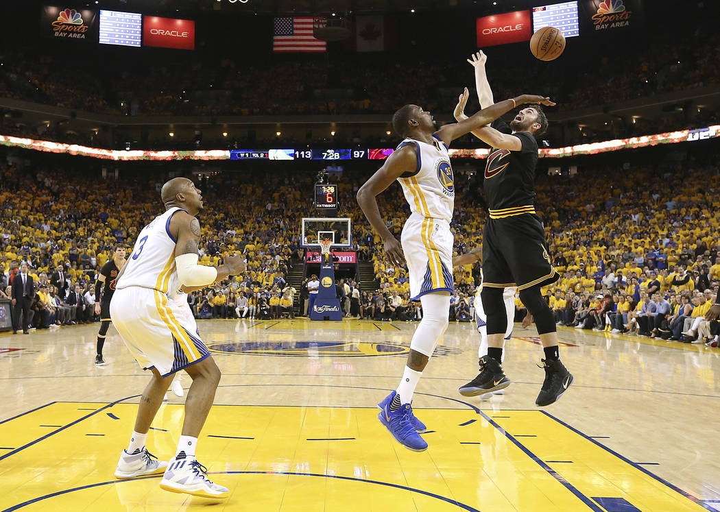 Golden State Warriors forward Kevin Durant, center, defends a shot by Cleveland Cavaliers forward Kevin Love during the second half of Game 2 of basketball's NBA Finals in Oakland, Calif., Sunday, ...