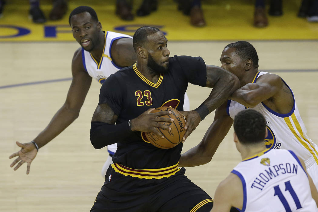 Cleveland Cavaliers forward LeBron James (23) shoots between Golden State Warriors forward Draymond Green, top, guard Klay Thompson (11) and forward Kevin Durant during the first half of Game 2 of ...