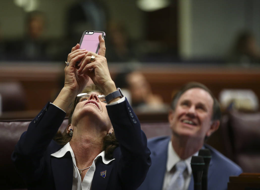 Assemblywoman Robin Titus, R-Wellington, takes a photo as the roll for Senate Bill 246 falls back during the final hour of the Nevada Legislature at the Legislative Building in Carson City on Mond ...