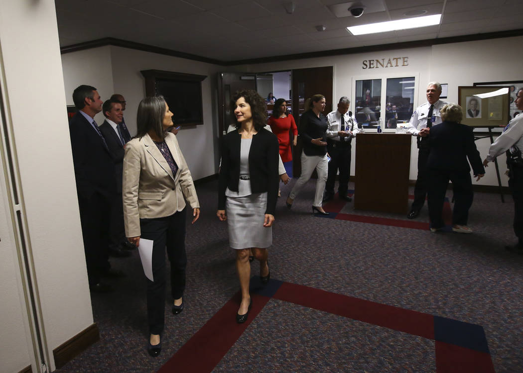 Sen. Julia Ratti, D-Sparks, left, and Sen. Heidi Gansert, R-Reno, make their way to the Assembly chambers to deliver the message to end the session during the final minutes of the Nevada Legislatu ...