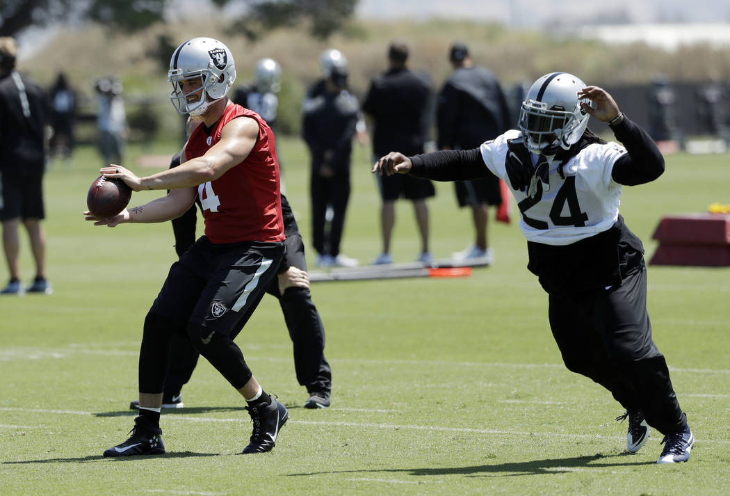 Oakland Raiders quarterback Derek Carr, left, and running back Marshawn Lynch go through drills during the team's organized team activity at its NFL football training facility Tuesday, June 6, 201 ...