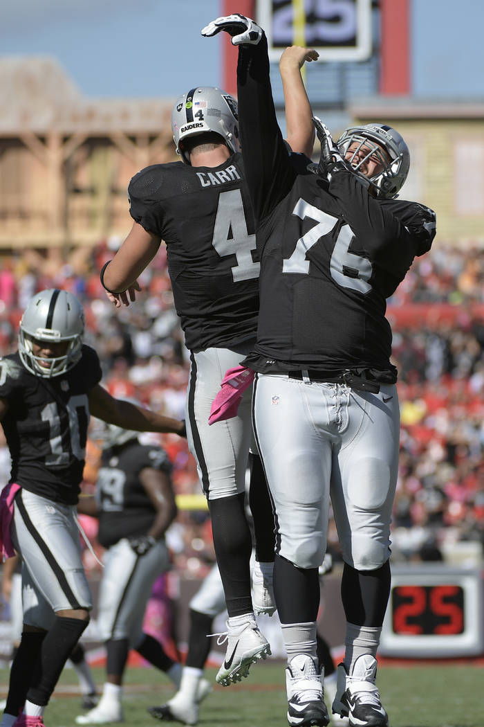Oakland Raiders quarterback Derek Carr (4) celebrates with offensive guard Jon Feliciano (76) after throwing a 1-yard touchdown pass to tackle Donald Penn (72) during the second half of an NFL foo ...