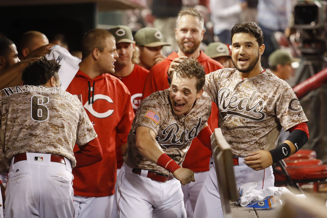 Cincinnati Reds' Scooter Gennett, center, celebrates in the dugout after hitting a two-run home run and his fourth overall in the eighth inning of a baseball game against the St. Louis Cardinals,  ...