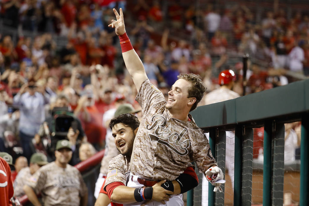 Cincinnati Reds' Scooter Gennett, center, is lifted up by Eugenio Suarez as he celebrates in the dugout during the eighth inning of a baseball game against the St. Louis Cardinals, Tuesday, June 6 ...
