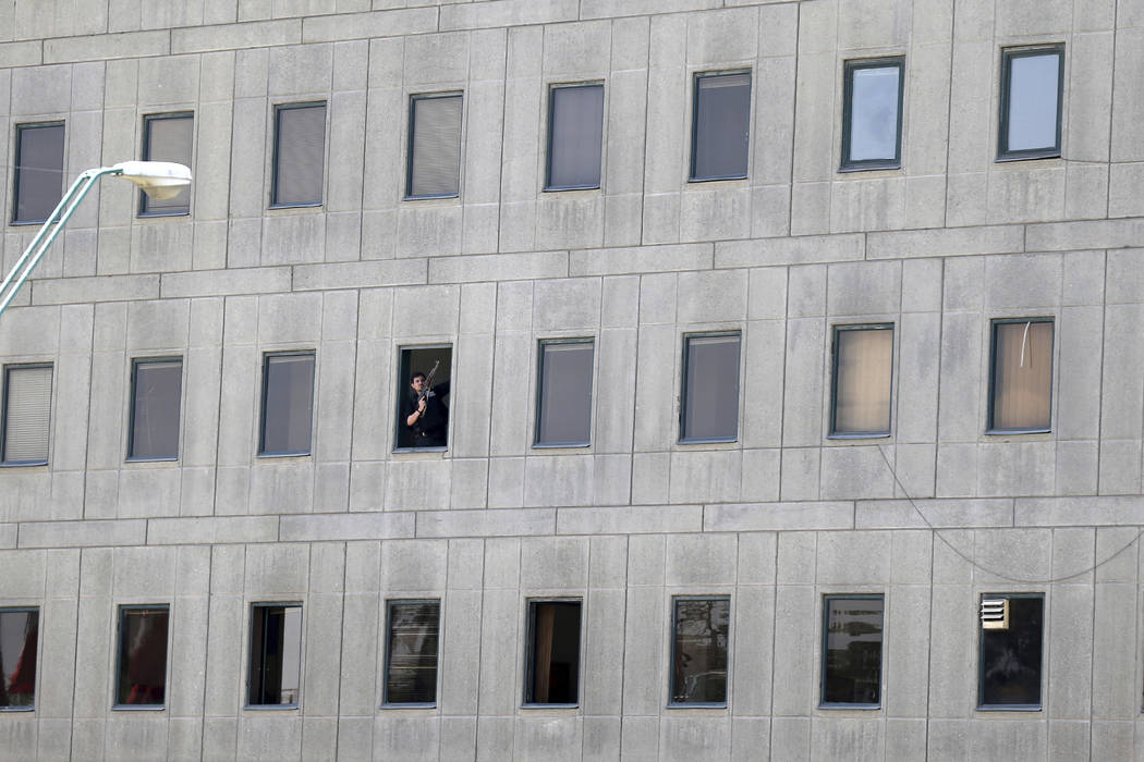 An armed man stands in a window of the parliament building in Tehran, Iran, Wednesday, June 7, 2017. Several attackers stormed into Iran's parliament and a suicide bomber targeted the shrine of Ay ...
