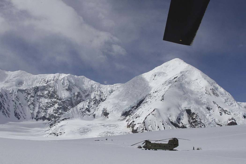 FILE - This April 24, 2016 file photo on the Kahiltna Glacier in Alaska, shows Army soldiers unloading a Chinook helicopter that landed on the glacier near Denali under the rotor blade of another  ...