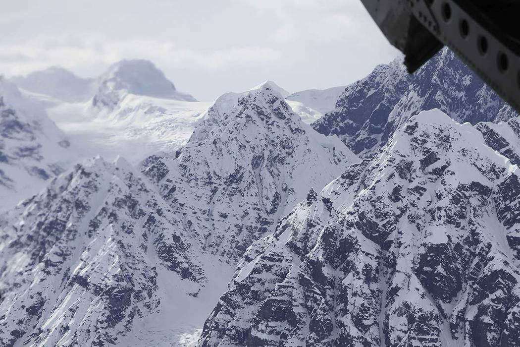 FILE - This April 24, 2016, file photo taken above the Kahiltna Glacier near Denali, shows peaks in the Alaska Range, as seen through the open cargo bay doors of a Chinook helicopter. Rangers resc ...
