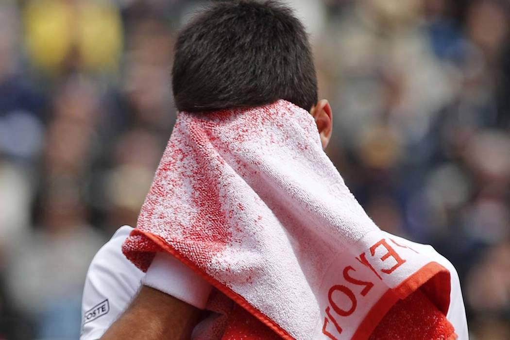 Serbia's Novak Djokovic wipes his face as he plays Austria's Dominic Thiem during their quarterfinal match the French Open tennis tournament at the Roland Garros stadium, Wednesday, June 7, 2017 i ...