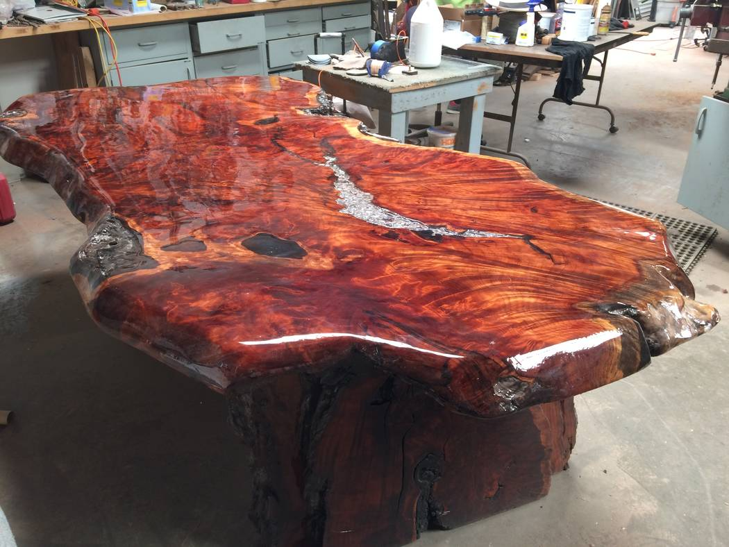 A commissioned piece, a table made from a slice of tree, is seen April 2017. Kyle Stinnett will smoke a cigar and contemplate on a piece of raw wood before deciding what it should become. He ensur ...