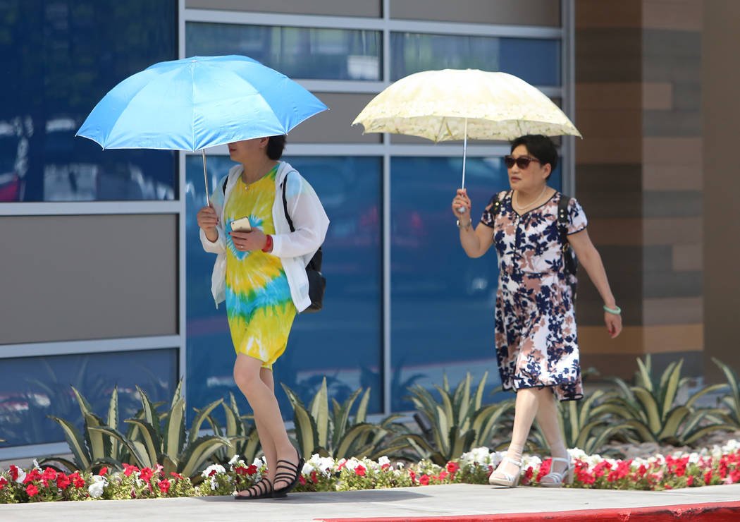 Pedestrians protect themselves from the sun as they walk on Sahara Avenue, near Palace Station hotel-casino, on Wednesday, June 7, 2017, in Las Vegas. (Bizuayehu Tesfaye/Las Vegas Review-Journal)  ...