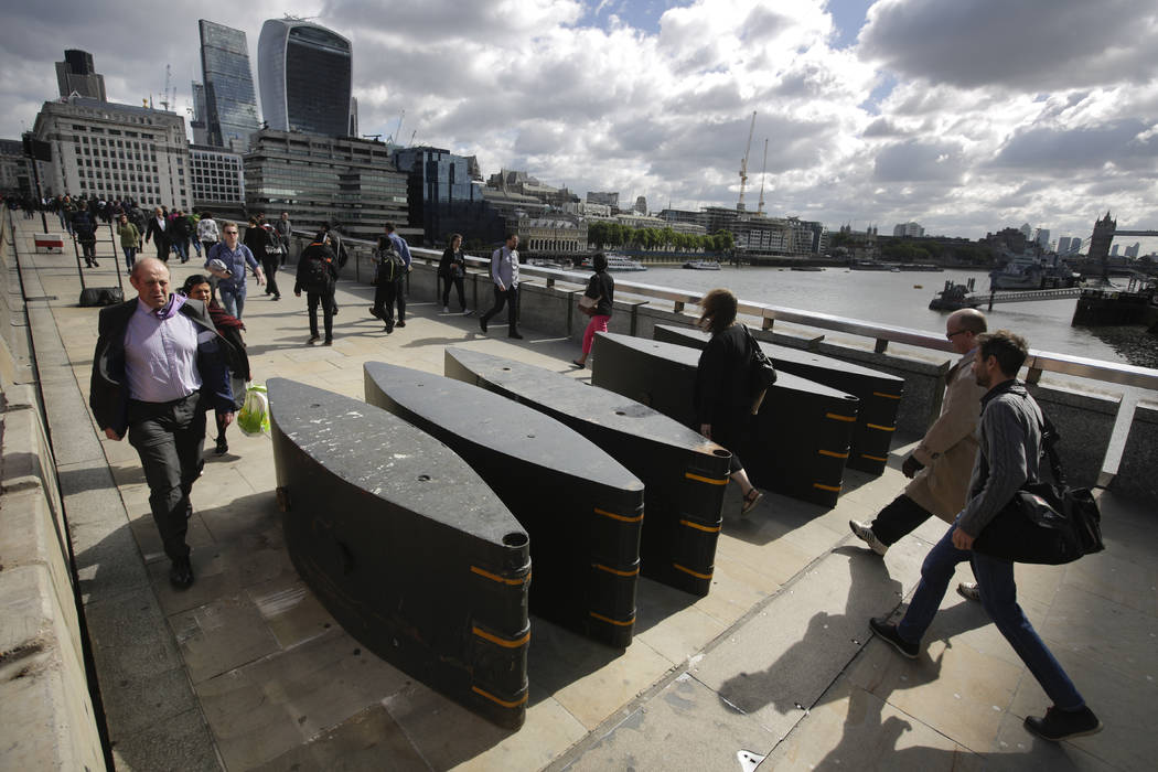 People walk through the barriers as they cross London Bridge in London, Wednesday, June 7, 2017. Much of the area around London Bridge remained cordoned off as police continued to investigate Satu ...