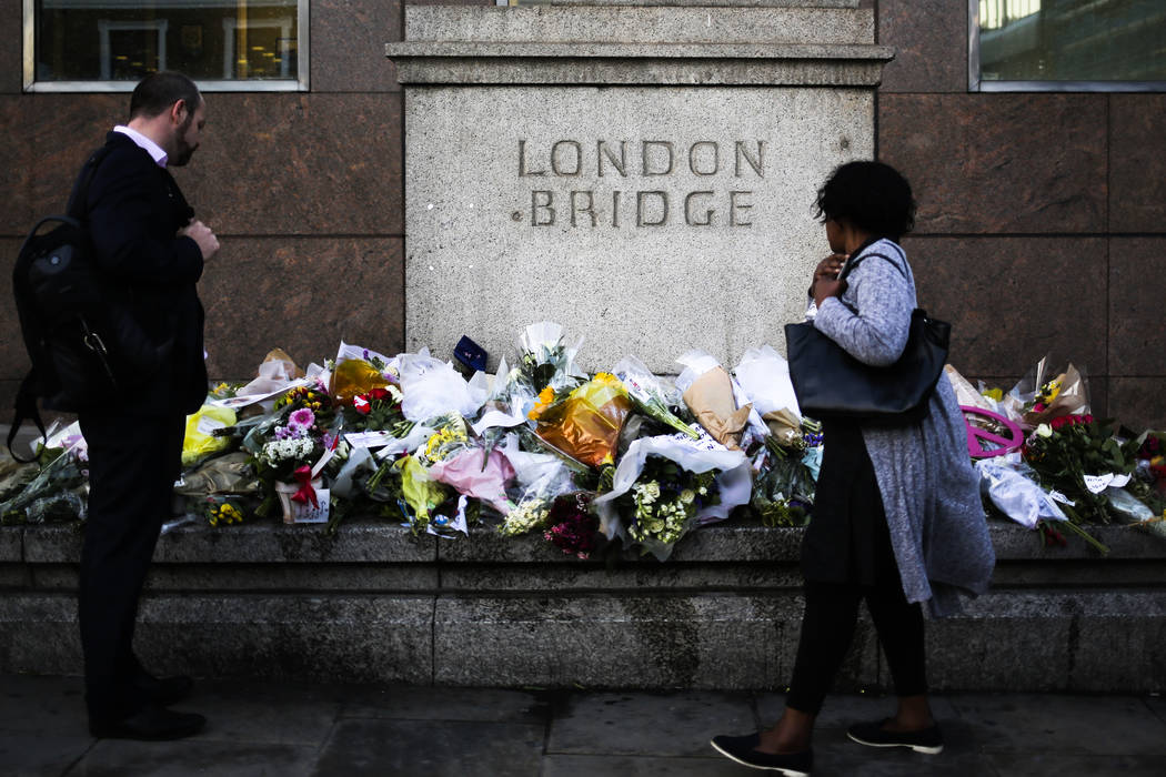 People look at the floral tributes placed at London Bridge to commemorate the victims of Saturday's attack in London, Tuesday, June 6, 2017. (Markus Schreiber/AP)