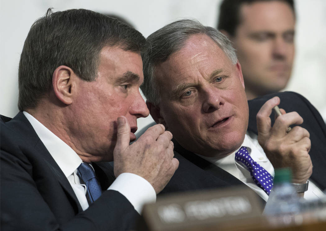 Senate Intelligence Committee Vice Chairman Mark Warner, D-Va., left, confers with Chairman Sen. Richard Burr, R-N.C., as the panel questions top national security chiefs about the gathering of in ...