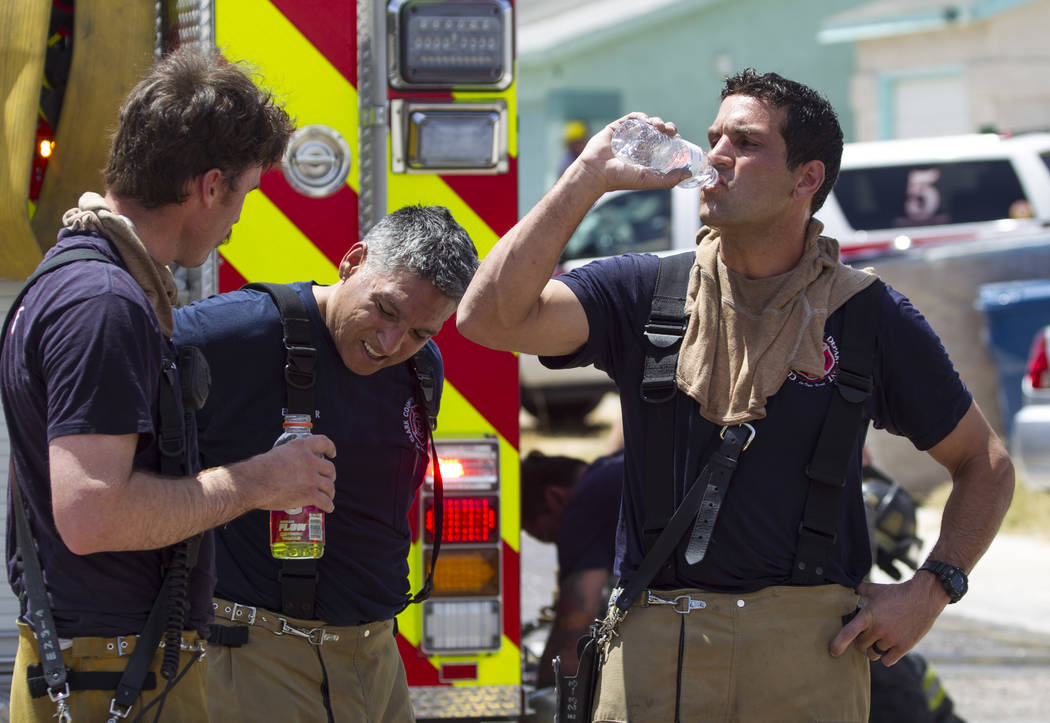 Clark County firefighters cool off after fighting a two-house fire in the 3600 block of Three Bars Court on Wednesday, June 7, 2017. (Richard Brian Las Vegas Review-Journal) @vegasphotograph