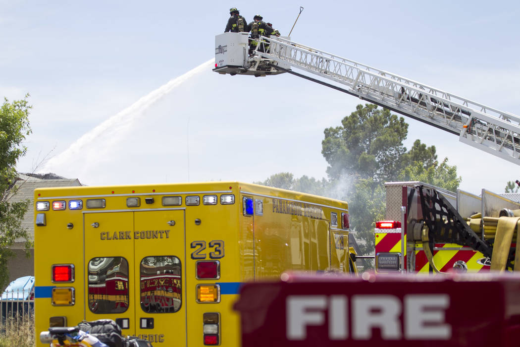 Clark County firefighters pour water on a two-house fire in the 3600 block of Three Bars Court in northeast Las Vegas on Wednesday, June 7, 2017. (Richard Brian Las Vegas Review-Journal) @vegaspho ...