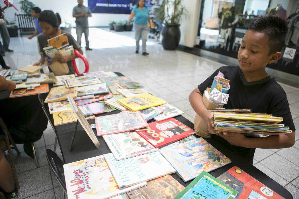 Eduardo Barragan, 9, holds a pile of books he picked out in part of Reading Rangers program at Boulevard Mall on Saturday, June 10, 2017 in Las Vegas. To promote summer reading, the program gives  ...