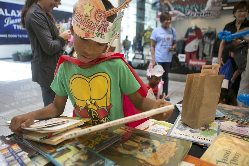 Xavier Rodriguez picks out books in part of Reading Rangers program at Boulevard Mall on Saturday, June 10, 2017 in Las Vegas. To promote summer reading, the program gives kids the opportunity to  ...