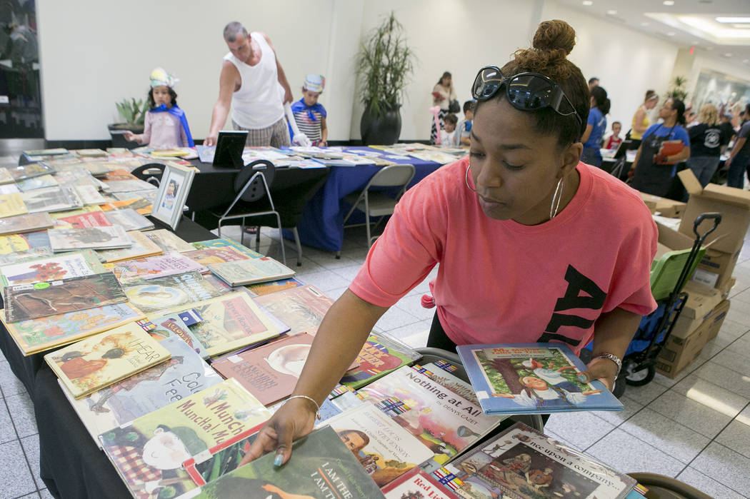 Teacher Kenisha Williams organizes books for kids in part of Reading Rangers program at Boulevard Mall on Saturday, June 10, 2017 in Las Vegas. To promote summer reading, the program gives kids th ...