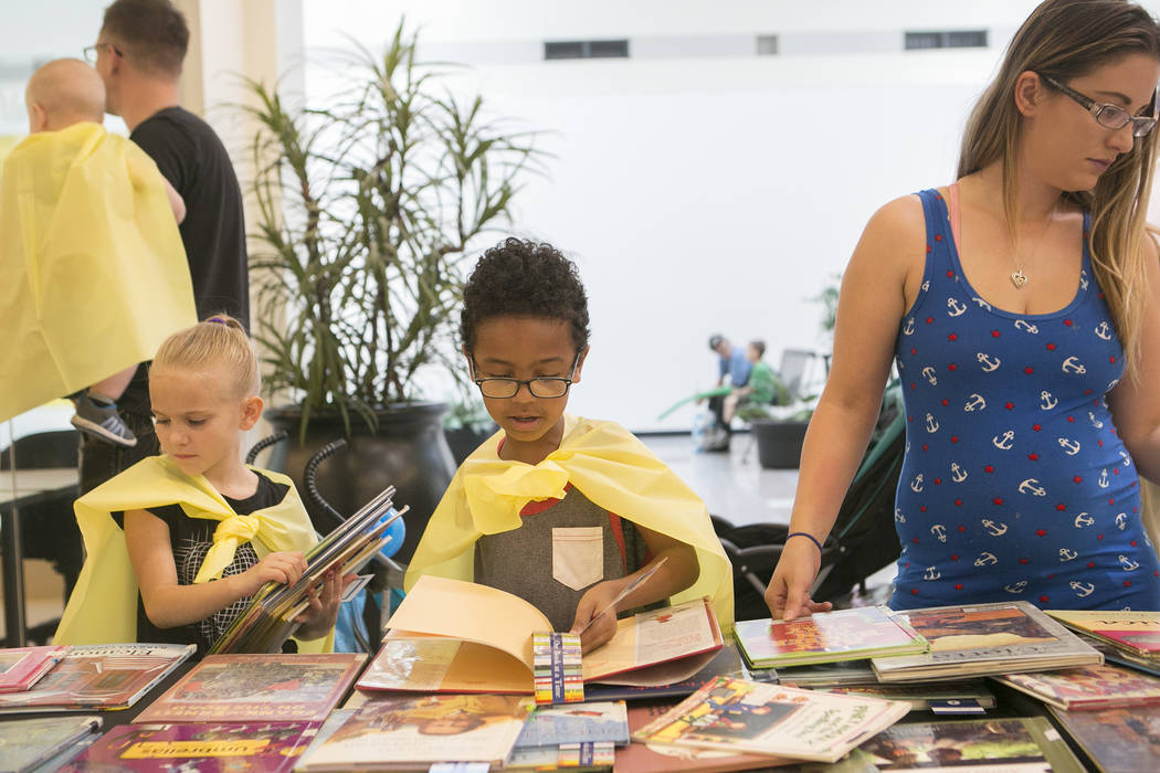 Davien Allen, 7, pages through a book while he chooses some to take home in part of Reading Rangers program at Boulevard Mall on Saturday, June 10, 2017 in Las Vegas. To promote summer reading, th ...