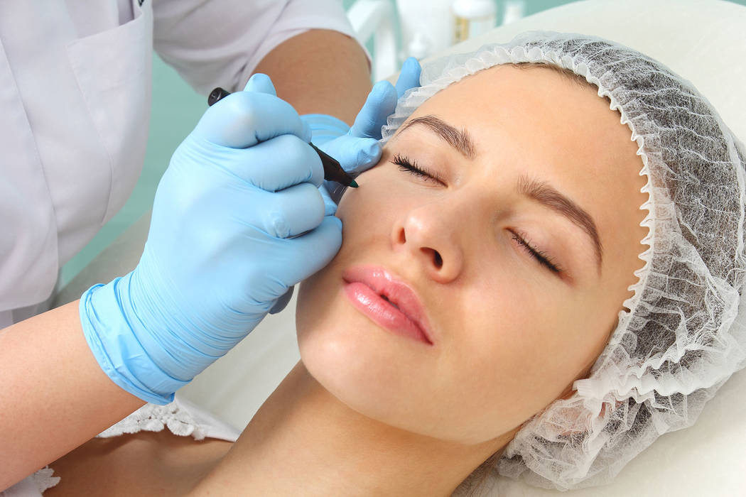 Plastic surgeon drawing lines over eyelid of a nice young female before cosmetic operation. (Thinkstock)