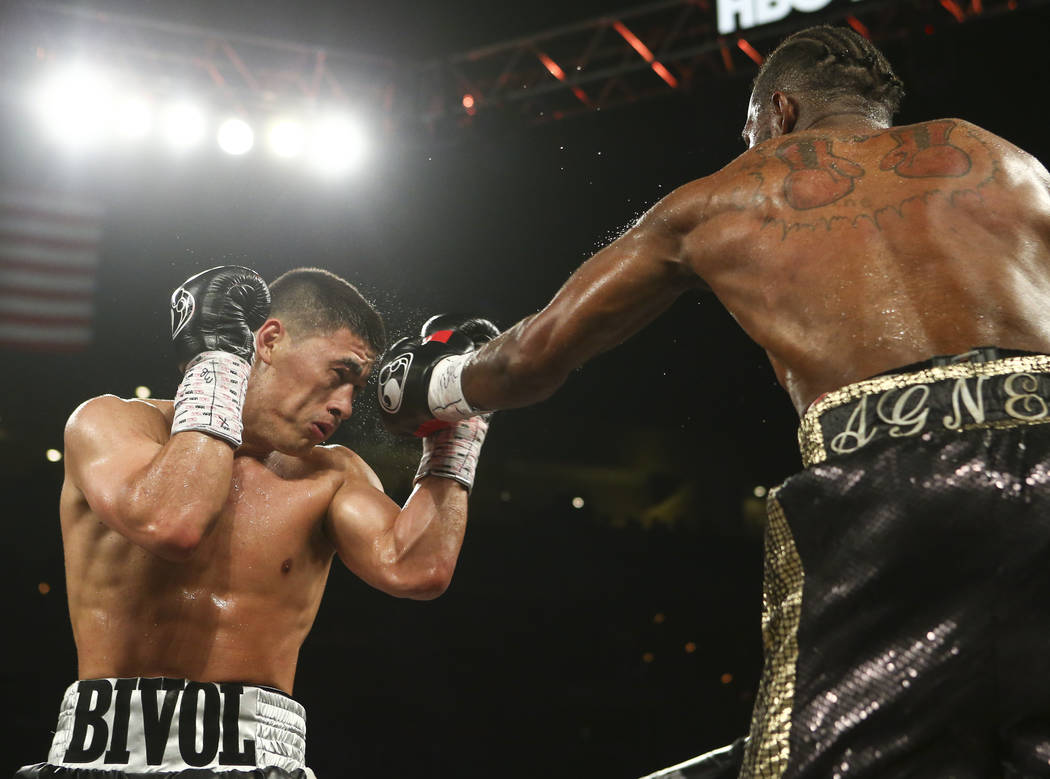 Dmitry Bivol, left, takes a hit from Cedric Agnew during their light heavyweight fight at the Mandalay Bay Events Center in Las Vegas on Saturday, June 17, 2017. Bivol won via technical knockout.  ...