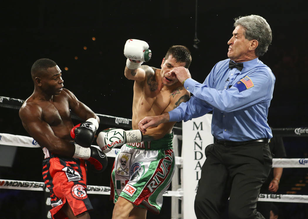 Moises Flores, center, is knocked out by Guillermo Rigondeaux in the first round as he falls towards referee Vic Drakulich during their super bantamweight title fight at the Mandalay Bay Events Ce ...