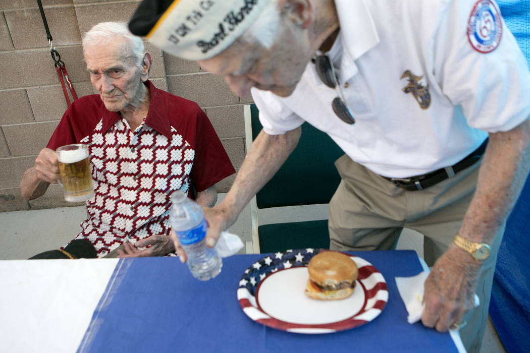 World War II veteran Allen Panowich, left, holds his beer while another WWII veteran Ed Hall, right, takes a seat during a BBQ party to celebrate Panowich's 101st birthday on Wednesday, June 7, 20 ...
